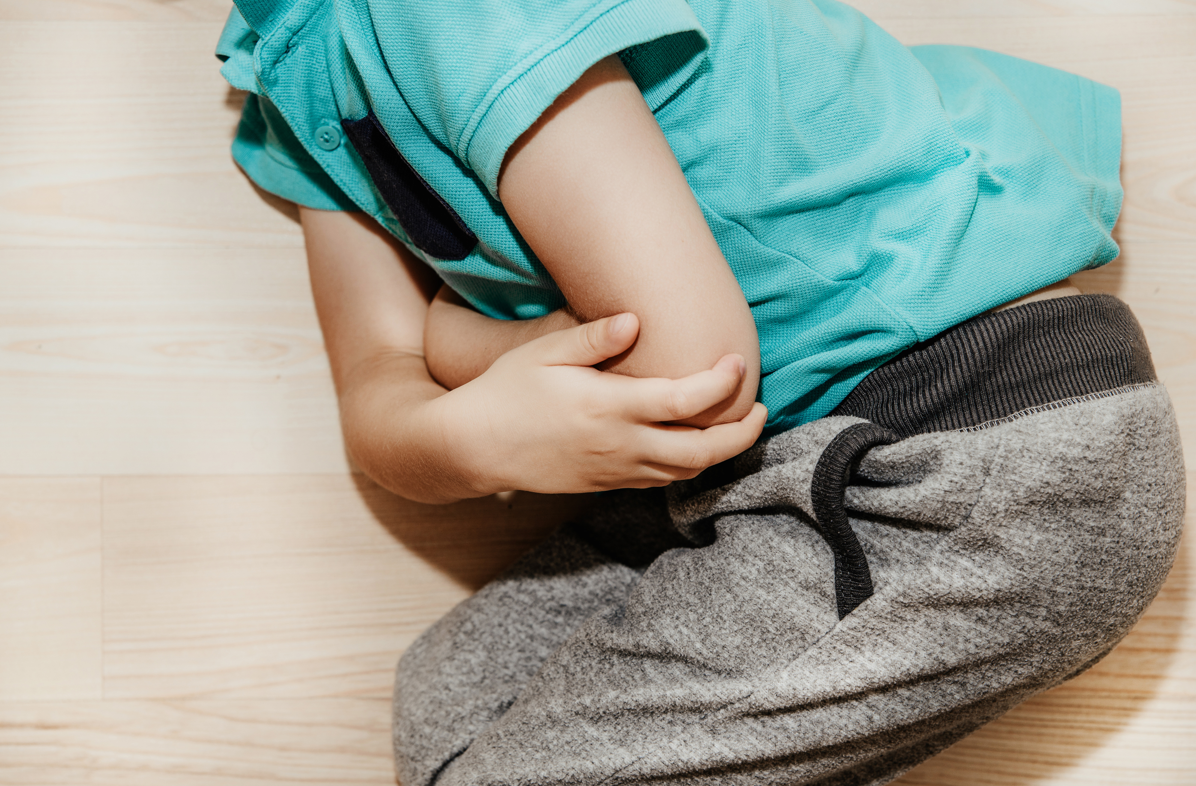 a child holding their stomach due to constipation - constipation in children