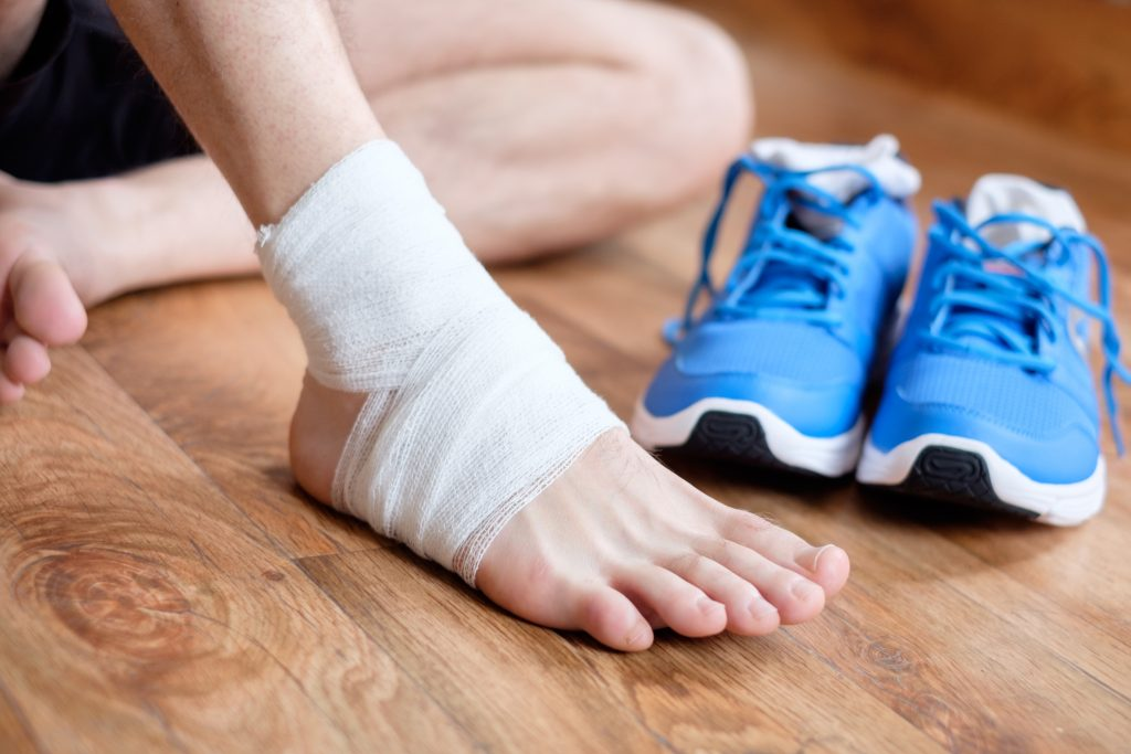 man with his injured sprained ankle